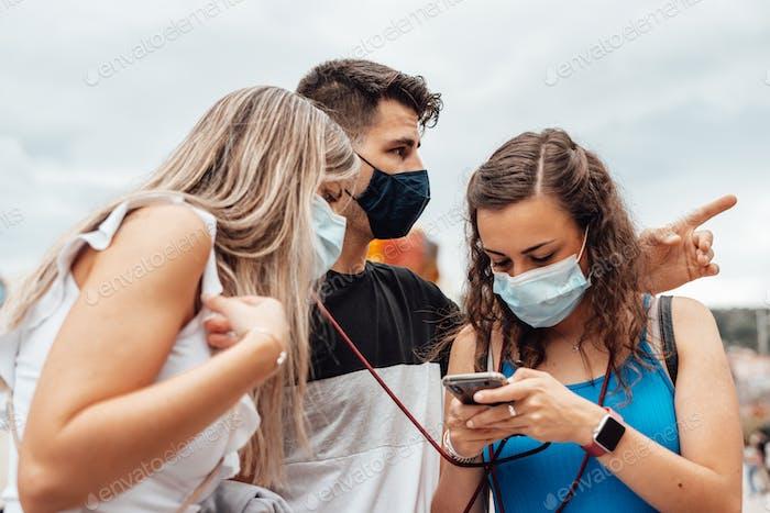 Gruppe von Freunden mit chirurgischen Masken suchen auf einem Smartphone