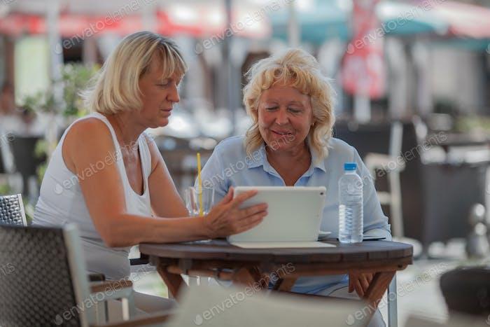 Seniorinnen entspannen im Café und mit digitalem Tablet