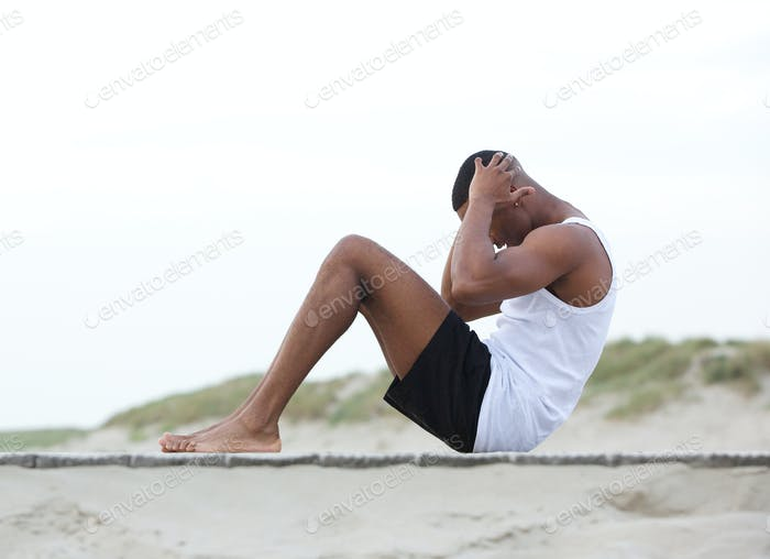Young man exercising on the beach doing sit ups