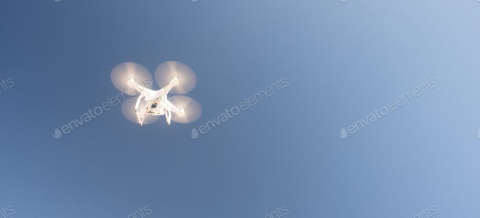 White UAV Quadcopter Drone in Flight Blue Sky