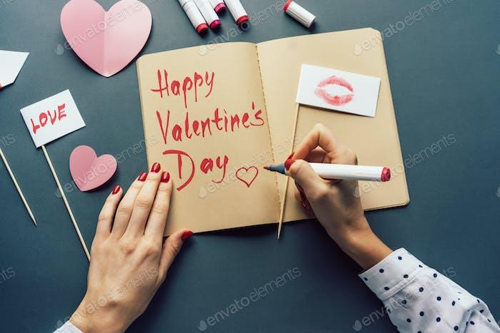 Frau schreibt einen Wunsch für den Valentinstag in einem Skizzenbuch.