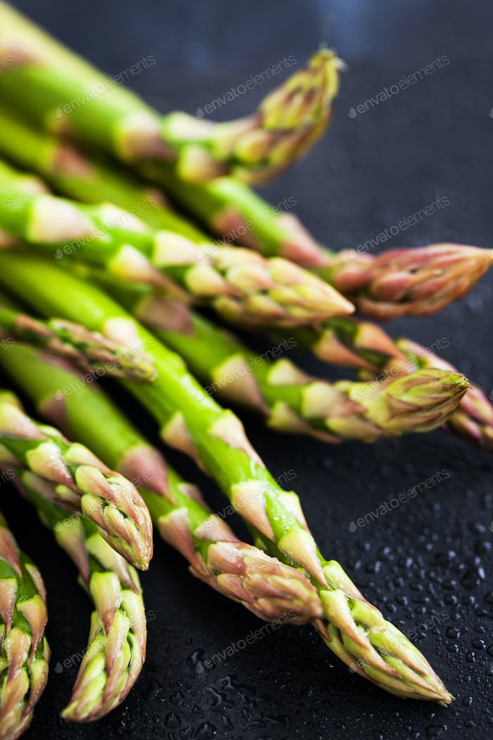 Raw fresh asparagus on dark background, close-up