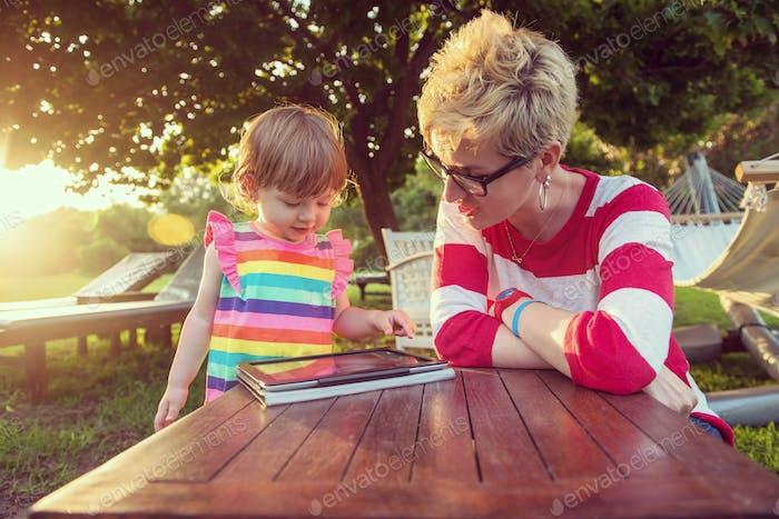 Mama und ihre kleine Tochter mit Tablet-Computer
