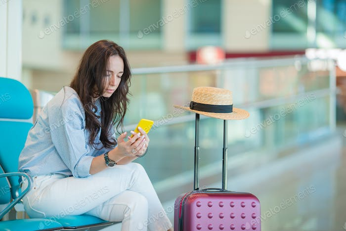 Young woman with smartphone in international airport waiting for flight aircraft