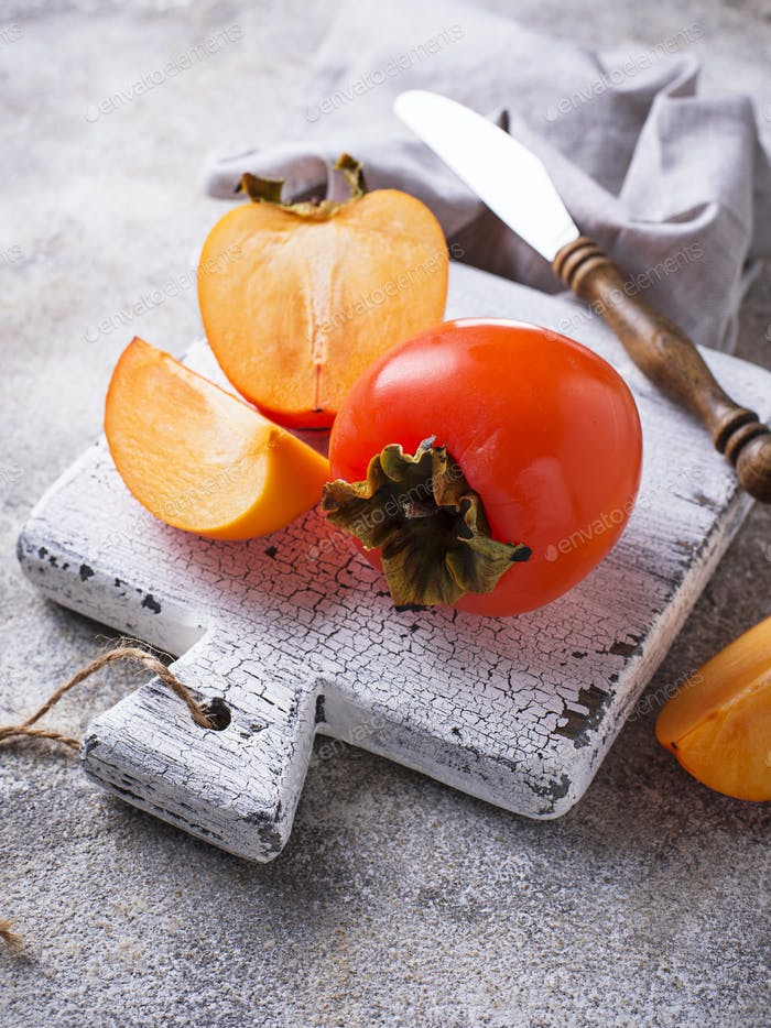 Fresh ripe persimmon on white cutting board