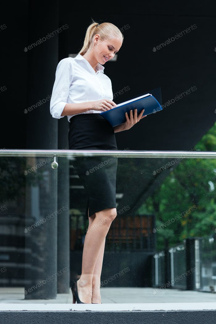 Cheerful businesswoman standing with folders at the glass balcony