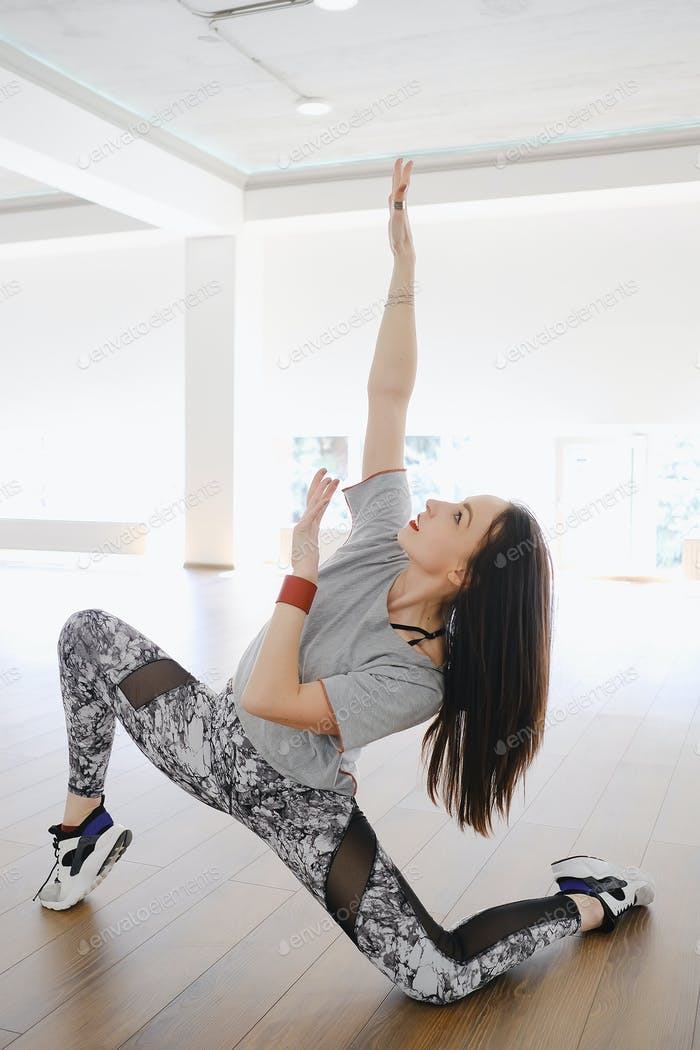 Athletic young girl practicing stretching and dance alone in a s