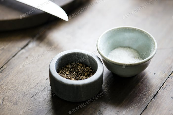 Two tiny bowls with salt and pepper