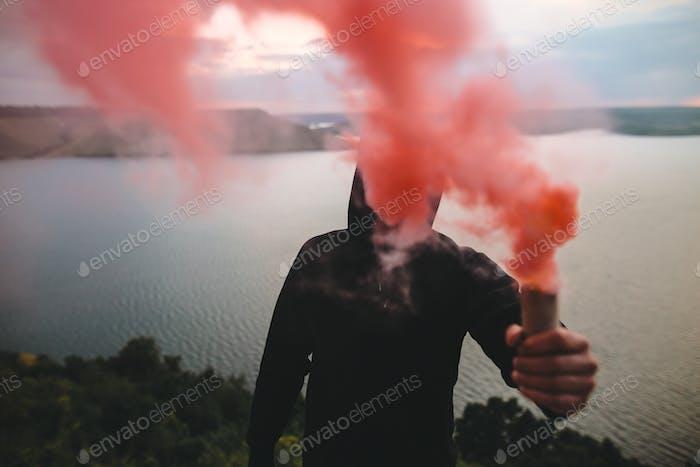 Ultras hooligan sosteniendo una bomba de humo roja en la mano con una vista increíble sobre el río