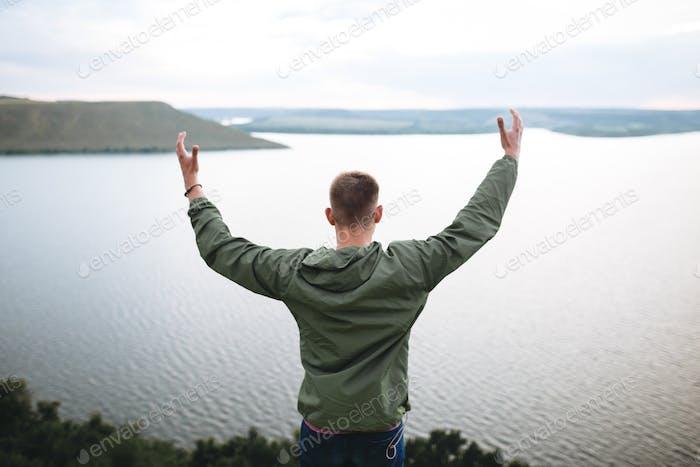 Hipster Reisende stehend auf dem Felsenberg genießen einen atemberaubenden Blick auf den Fluss