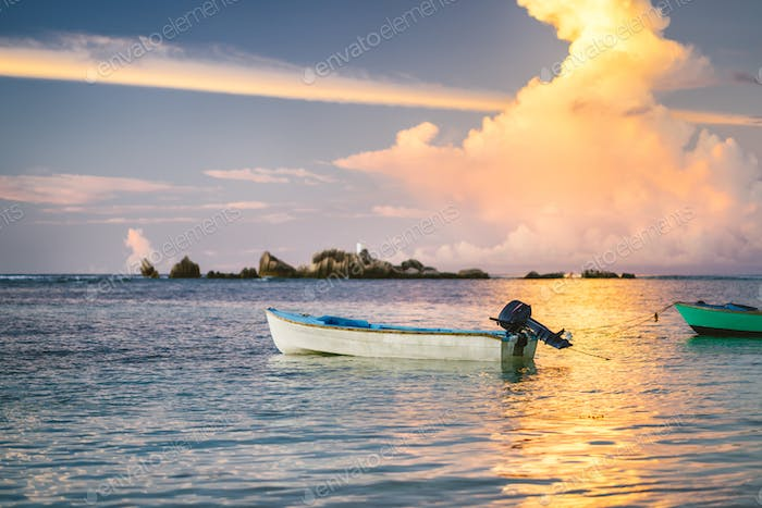 Purple golden clouds lit by sunset on La Digue. An fishing boat floats in ocean bay with fire colors