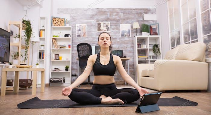 Tablet-Computer vor der jungen Frau tun Yoga