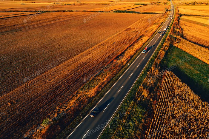Cars driving down the road through countryside in autumn