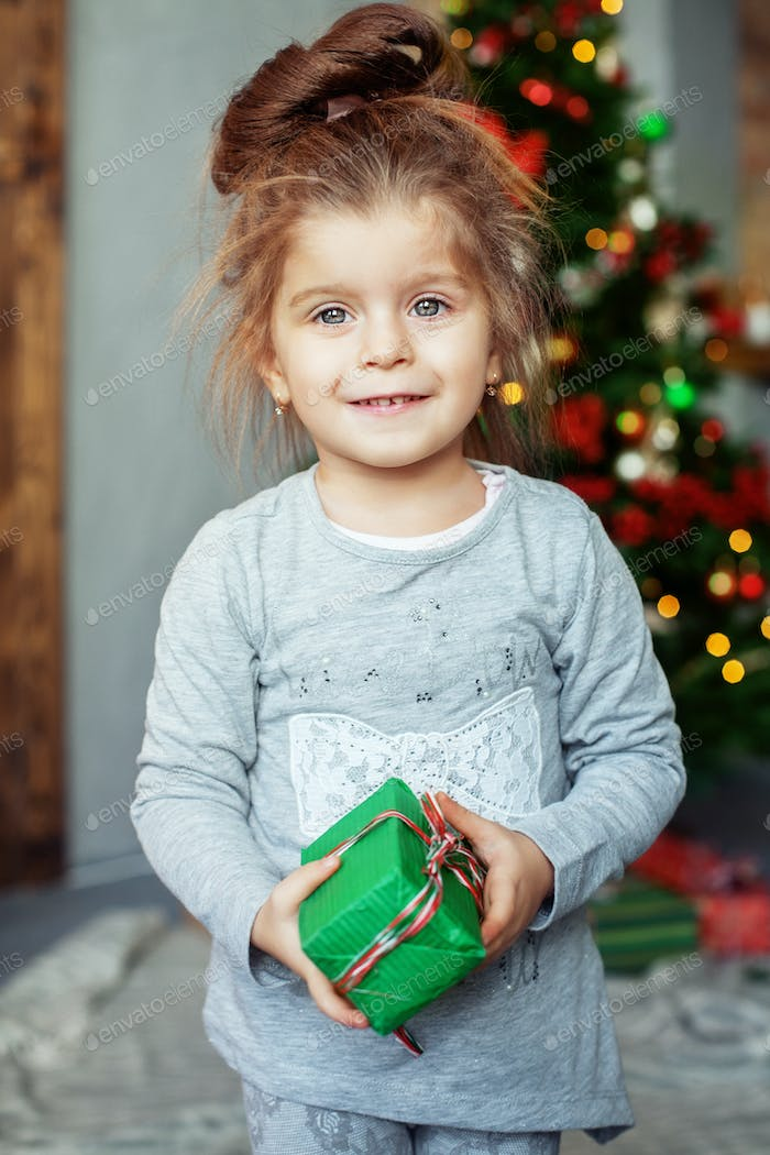 small child with a present. The concept of Christmas.