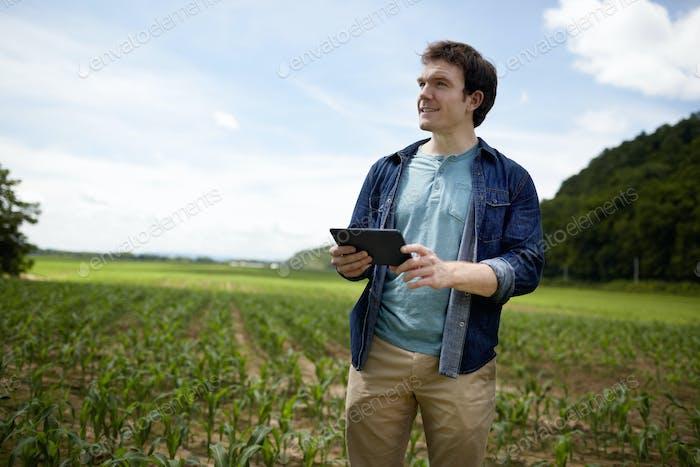Ein Landwirt hält ein digitales Tablet, Technologie in der Landwirtschaft, auf seinen Feldern in New York State, USA.