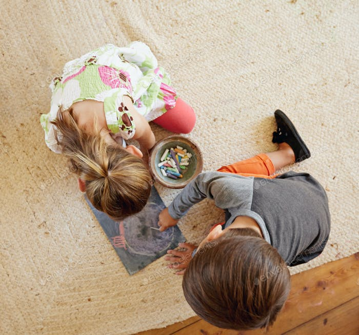 Little kids sitting on floor drawing with color chalks
