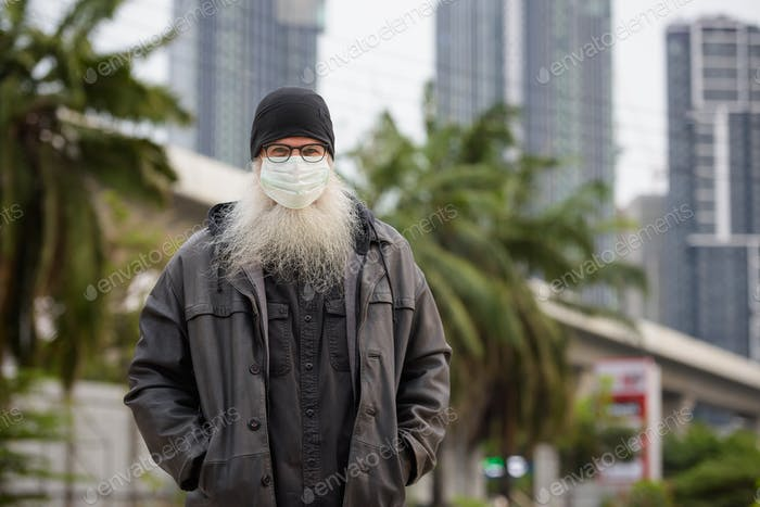 Mature bearded hipster man with mask for protection from corona virus outbreak