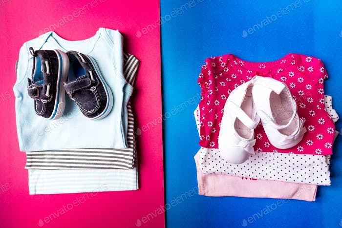 Folded blue and pink bodysuit.  Stack of infant clothing. Child outfit.