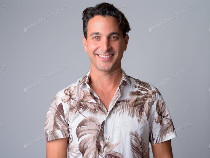 Face of happy handsome Hispanic tourist man smiling