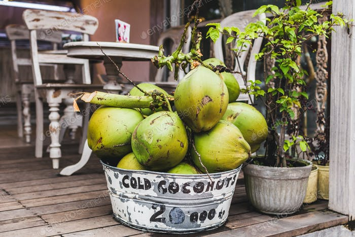 Basket with young green coconuts at the cafe entrance, hipster style