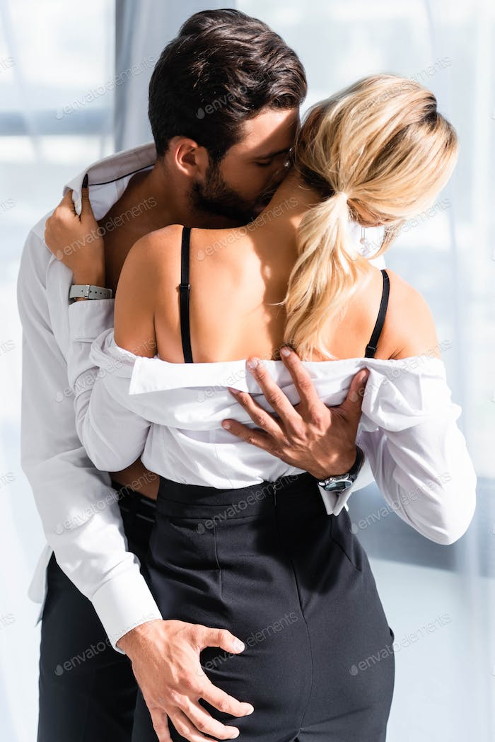 Businessman kissing and holding buttock of sexy woman