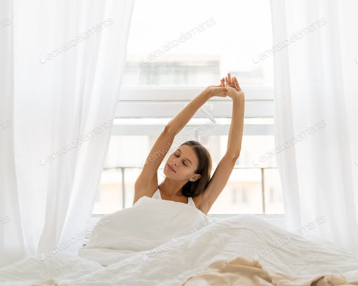 Young woman stretching in bed after wake up, entering new day happy