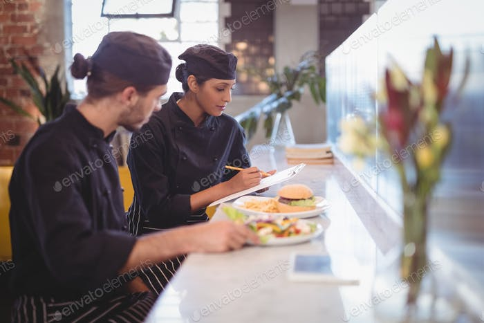 Young wait staff sitting with clipboard and food at counter