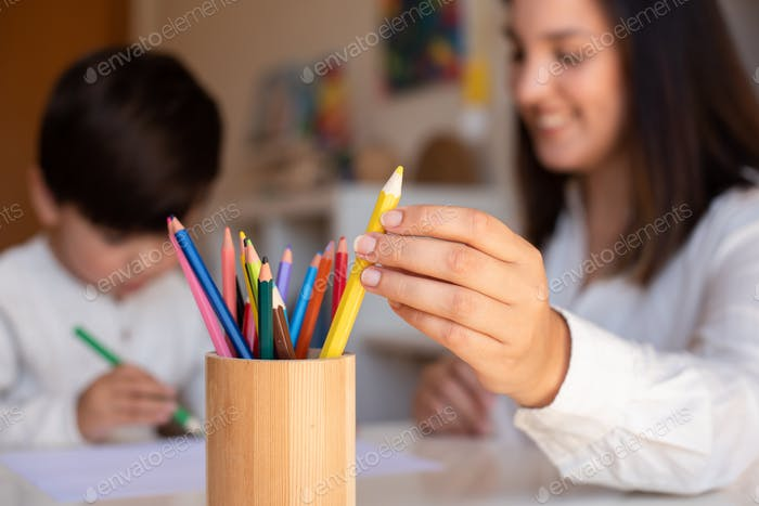 Preschooler kid drawing with coloured pencils with mother or teacher educator. Focus on the pencils.