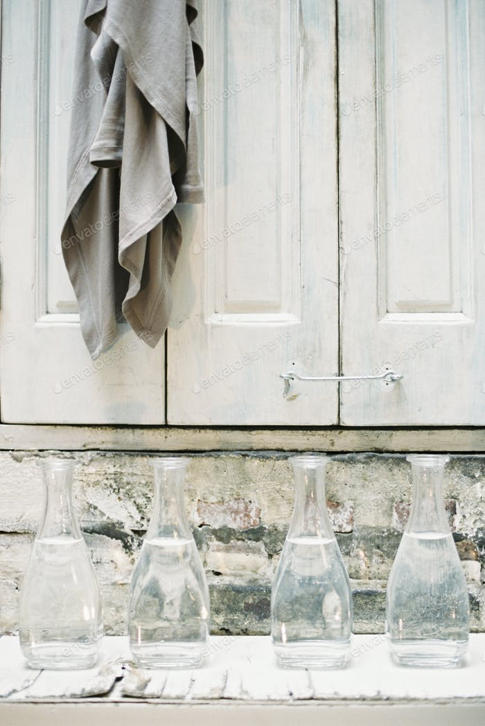 A cloth hanging from a peg on a a cupboard door, above a shelf of glass carafes.