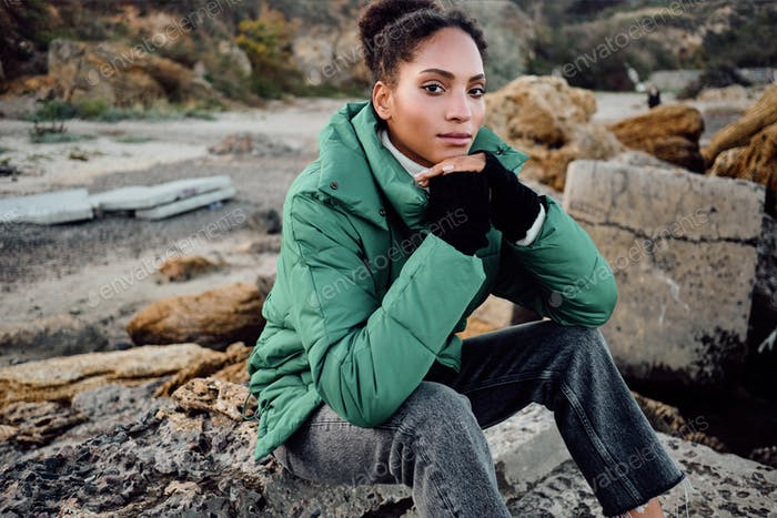 Stylish African American girl in down jacket confidently looking in camera sitting on rocks