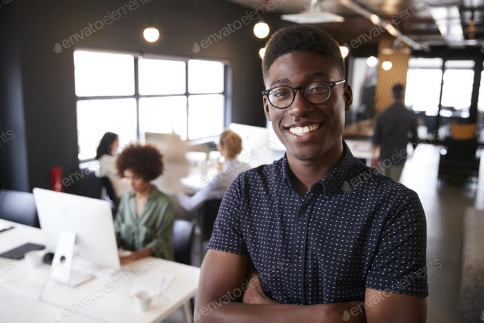 Millennial black male creative standing in a busy casual office, smiling to camera