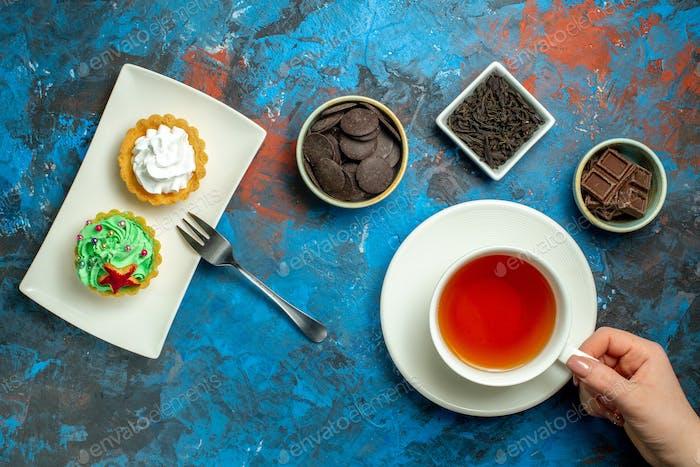 Draufsicht auf eine Tasse Tee kleine Kuchen Schokolade auf blauem rotem Hintergrund