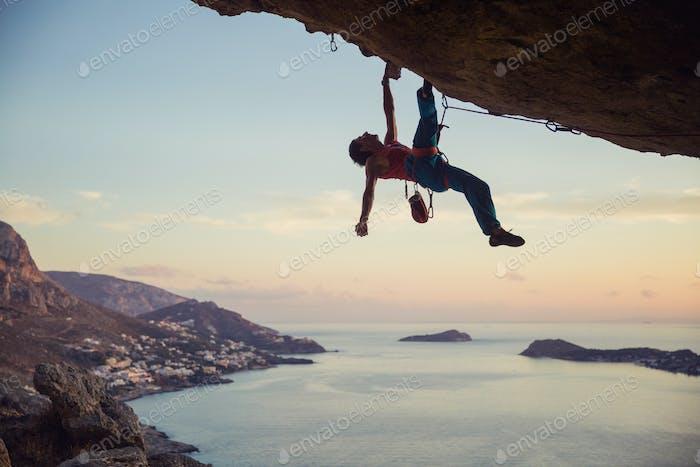 Junger Mann kämpfen, um anspruchsvolle Route auf Klippe zu klettern