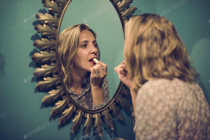 Blond woman putting on lipstick