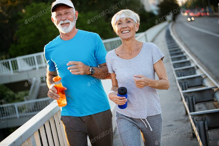 City running couple jogging outside. Senior couple runners training outdoors