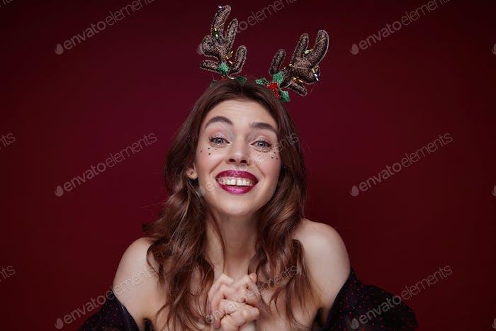 Indoor shot of young joyful lovely brunette with wavy hairstyle enjoying x-mas