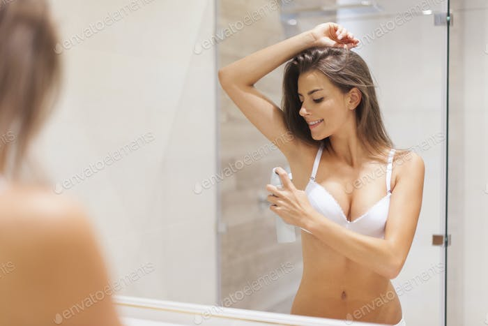 Happy woman using deodorant on underarm