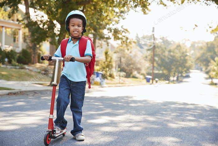 Young Boy Reiten Roller entlang Straße zur Schule
