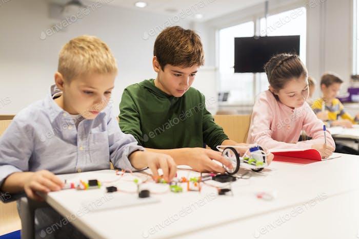glückliche Kinder bauen Roboter an der Roboterschule