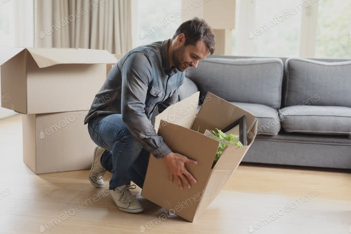 Side view of Caucasian man keeping down cardboard box in new home