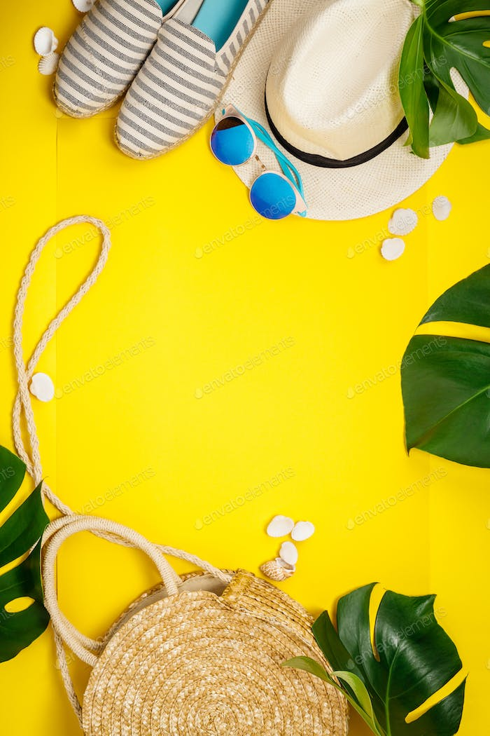 Straw hat, camera, bag, summer shoes, sunglasses, shells and tropical leaves over yellow background