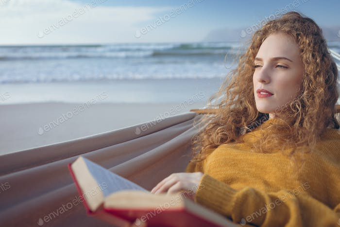 Woman holding book while lying on hammock at beach