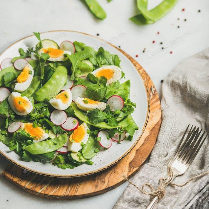 Green salad with radish, boiled egg, arugula, green pea, mint