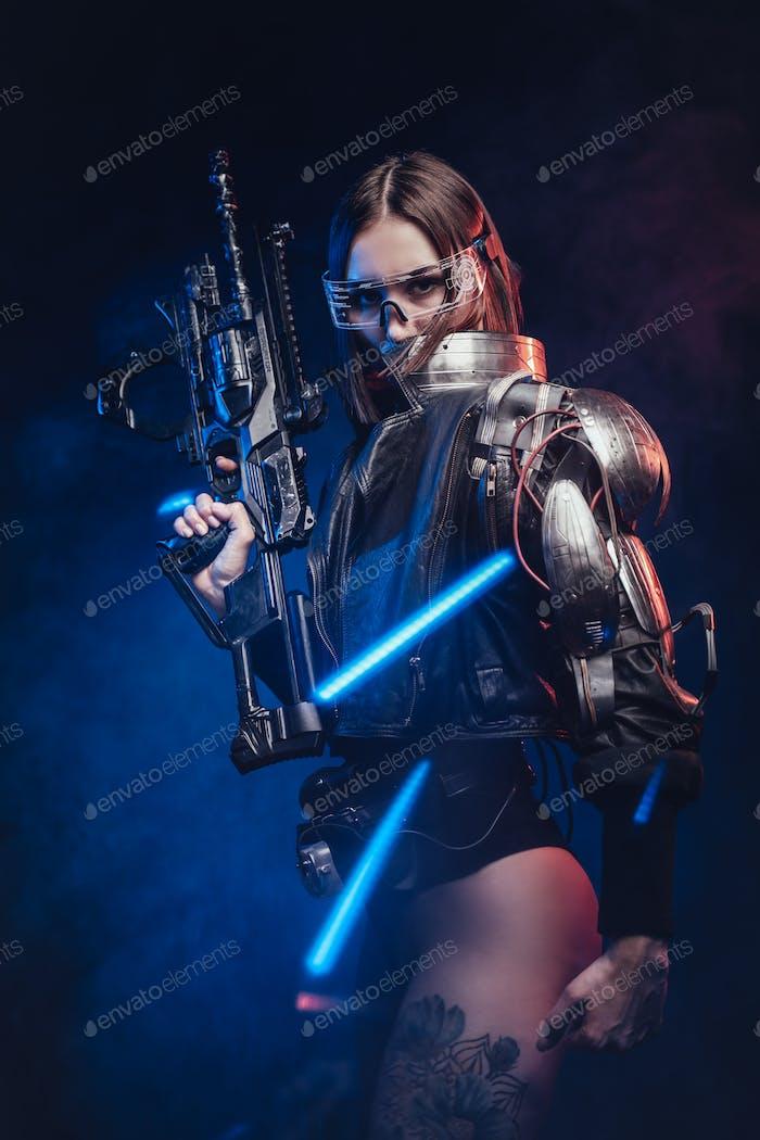 Futuristische Agentin bewaffnet mit Gewehr posiert auf dunklem Hintergrund