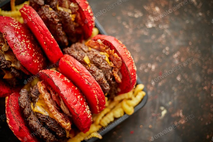 Set of four homemade giant double becon cheese burgers. Served with french fries on wooden board
