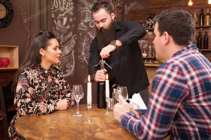 Hipster bearded bartender opening a bottle of wine for the clients
