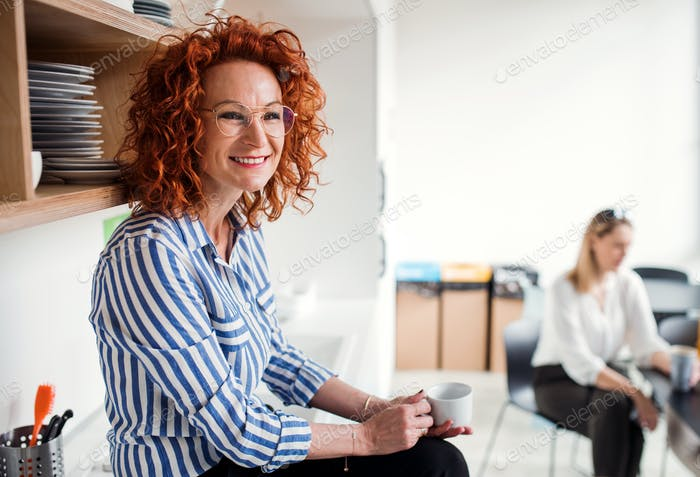 Mature businesswoman on coffee break in office kitchen, holding coffee