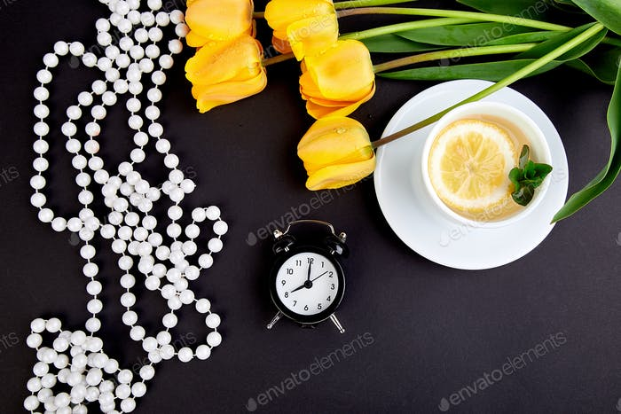Black alarm clock near bouquet yellow tulips