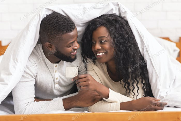 Black couple holding condom, lying on bed under white blanket