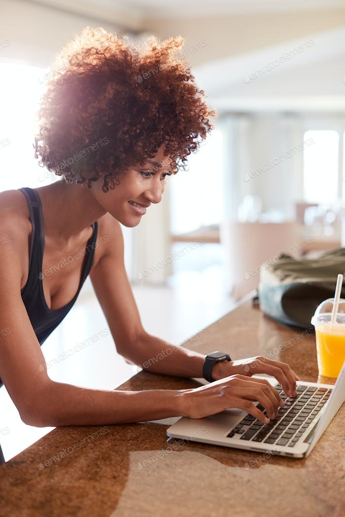 Millennial African American woman using laptop to check fitness data after her work out, vertical